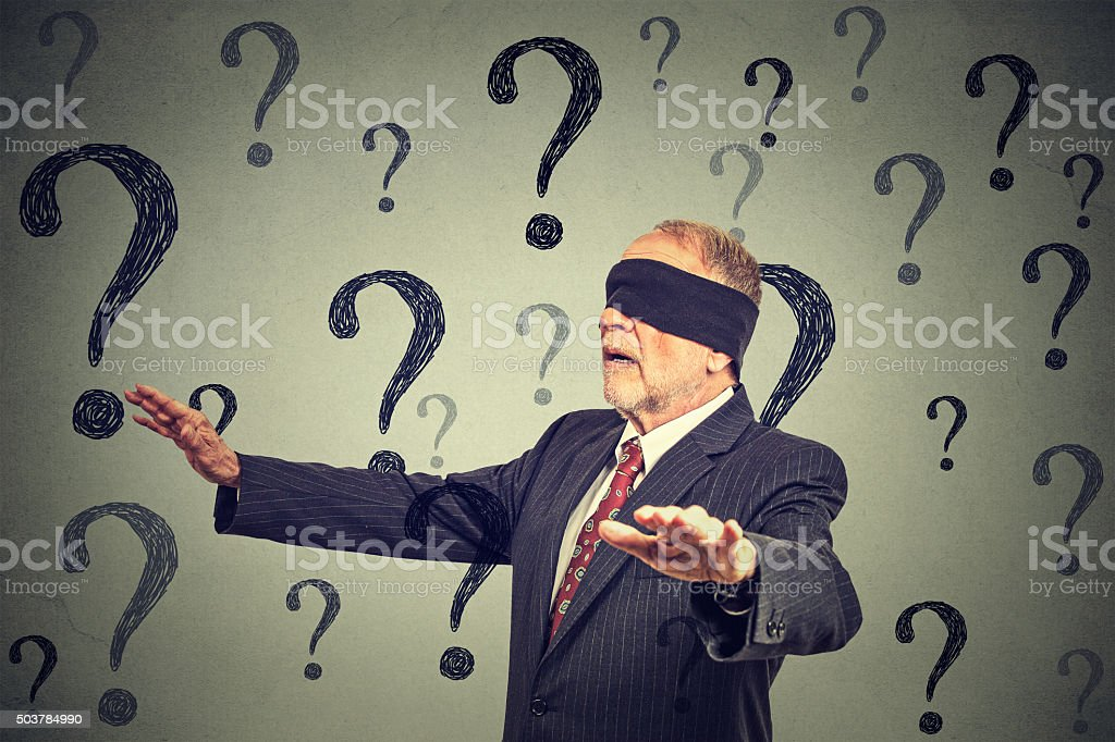 blindfolded business man walking through many questions stock photo