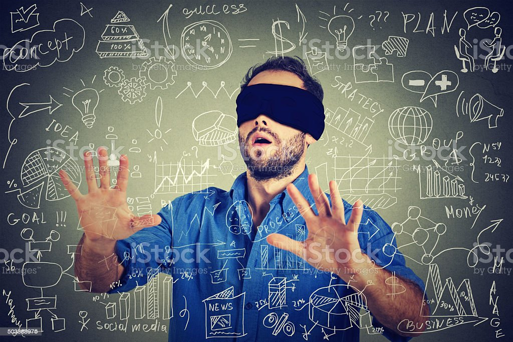 Blindfolded business man walking through social media financial data stock photo