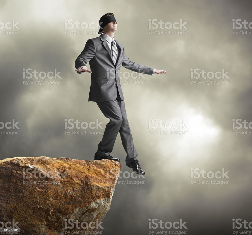 Blindfolded businessman about to step off of a cliff stock photo