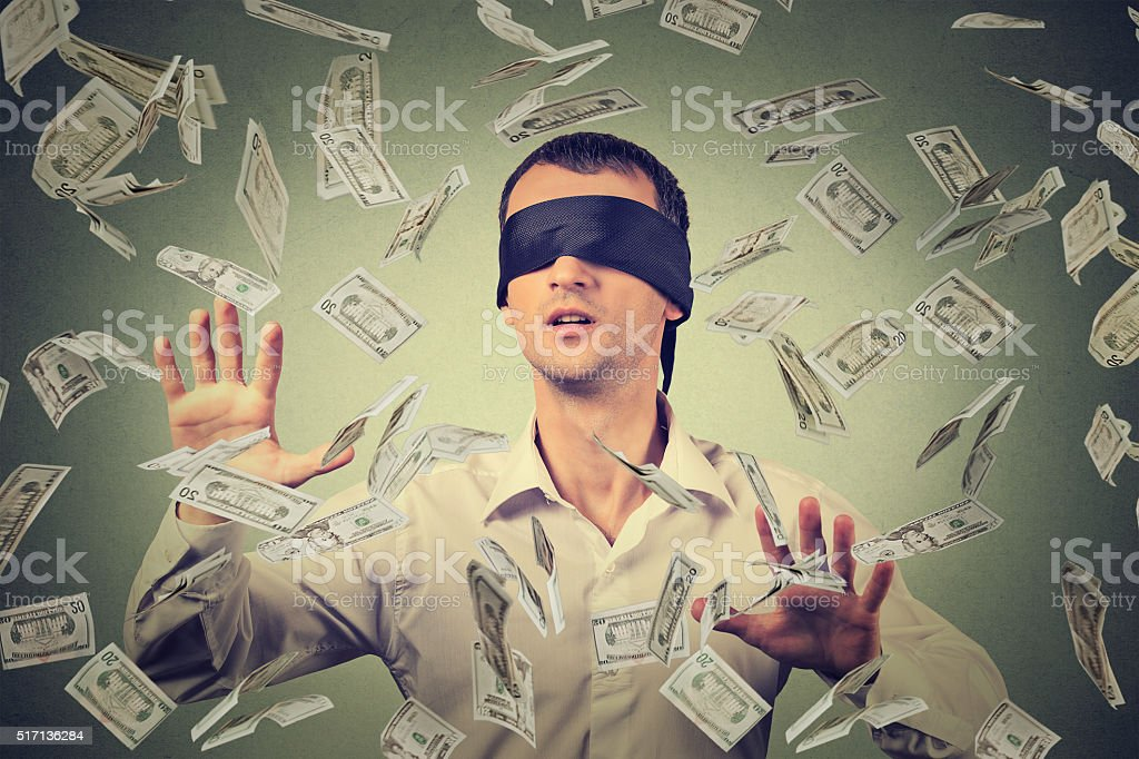 Blindfolded businessman trying to catch dollar bills banknotes stock photo