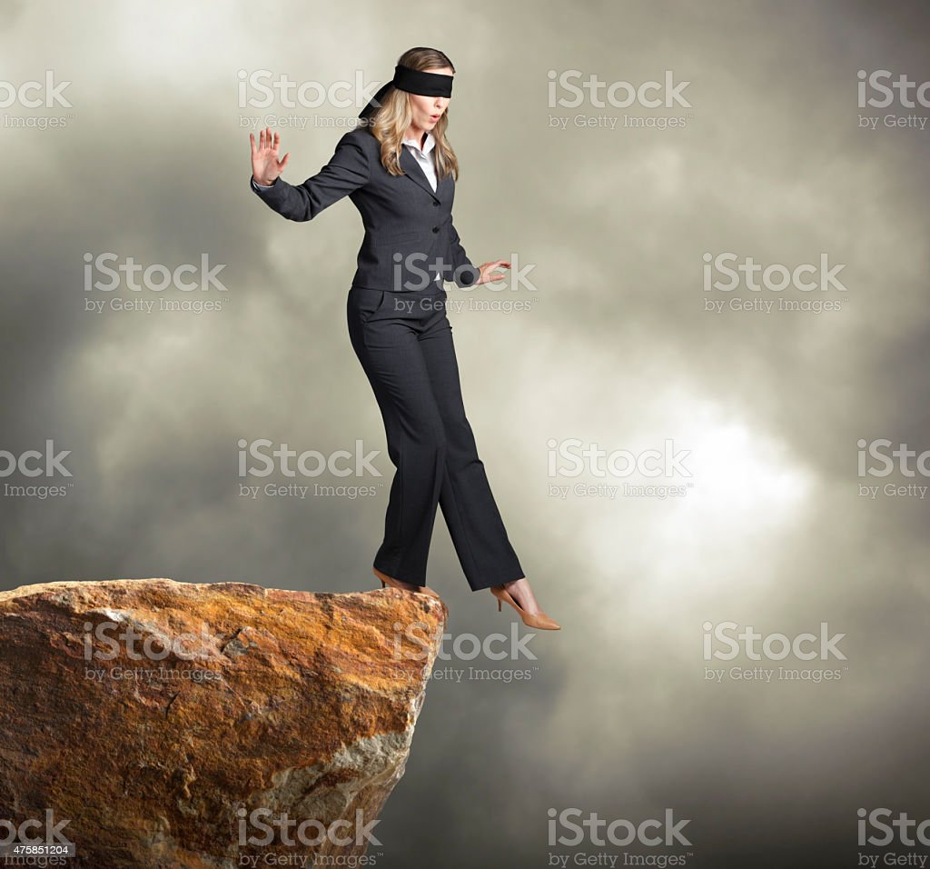 Blindfolded businesswoman about to step off of a clif stock photo