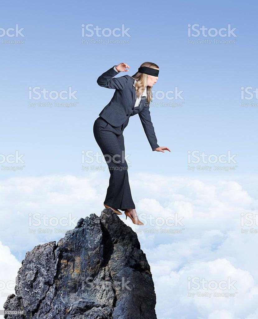 Blindfolded Businesswoman Balances On Mountain Top stock photo