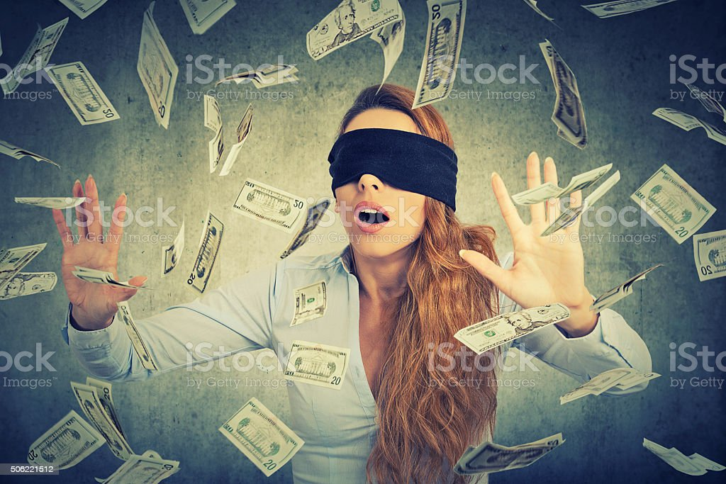 Blindfolded entrepreneur businesswoman trying to catch dollar bills stock photo