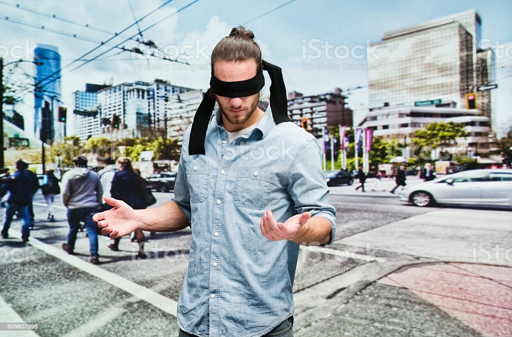 Blindfolded man standing on road stock photo