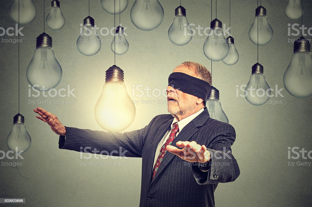 Blindfolded man walking through light bulbs searching for bright idea stock photo