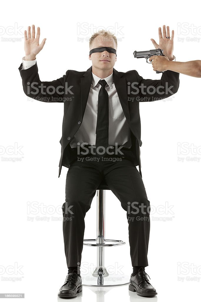 Blindfolded man with a gun pointing to his head royalty-free stock photo