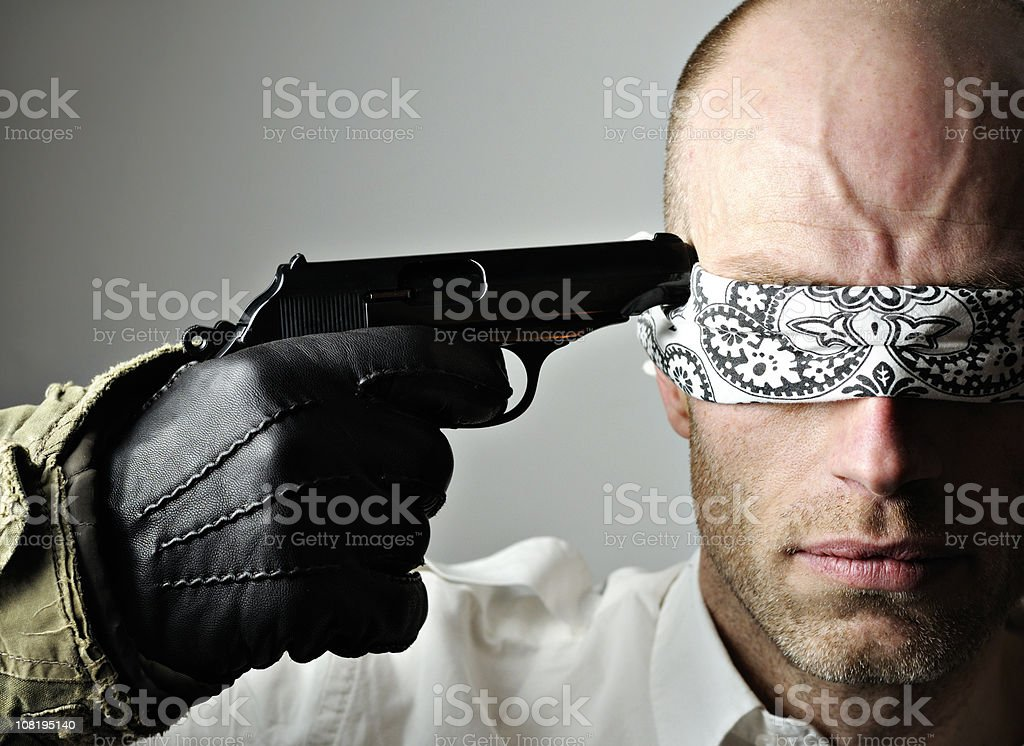 Blindfolded Man with Gun to Head royalty-free stock photo