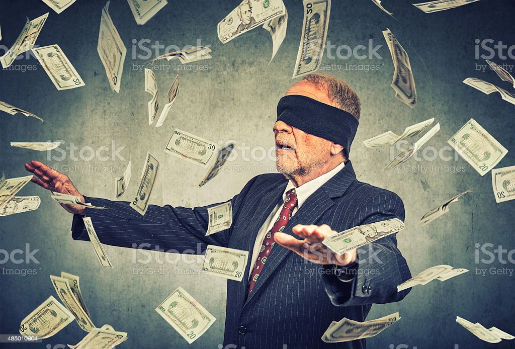 Blindfolded senior businessman trying to catch dollar bills banknotes stock photo