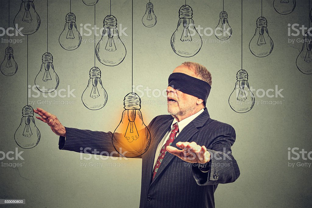 Blindfolded senior man walking through light bulbs searching for idea stock photo