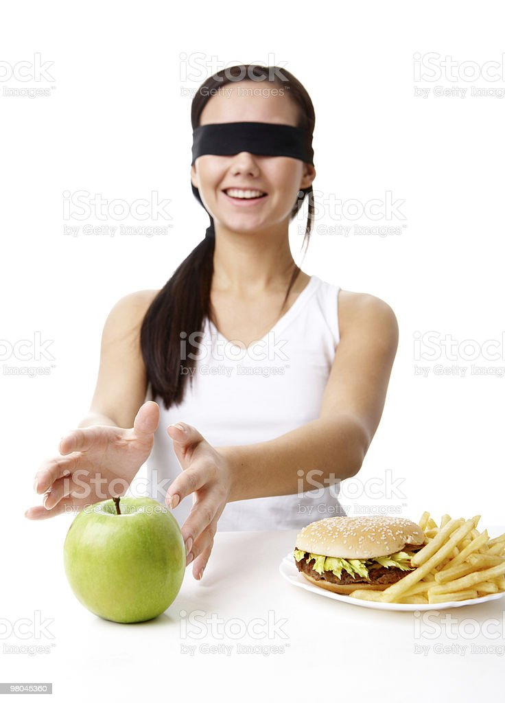 Blindfolded woman choosing green apple instead of burger royalty-free stock photo