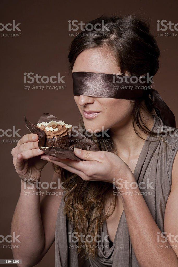 Blindfolded woman holding cake stock photo