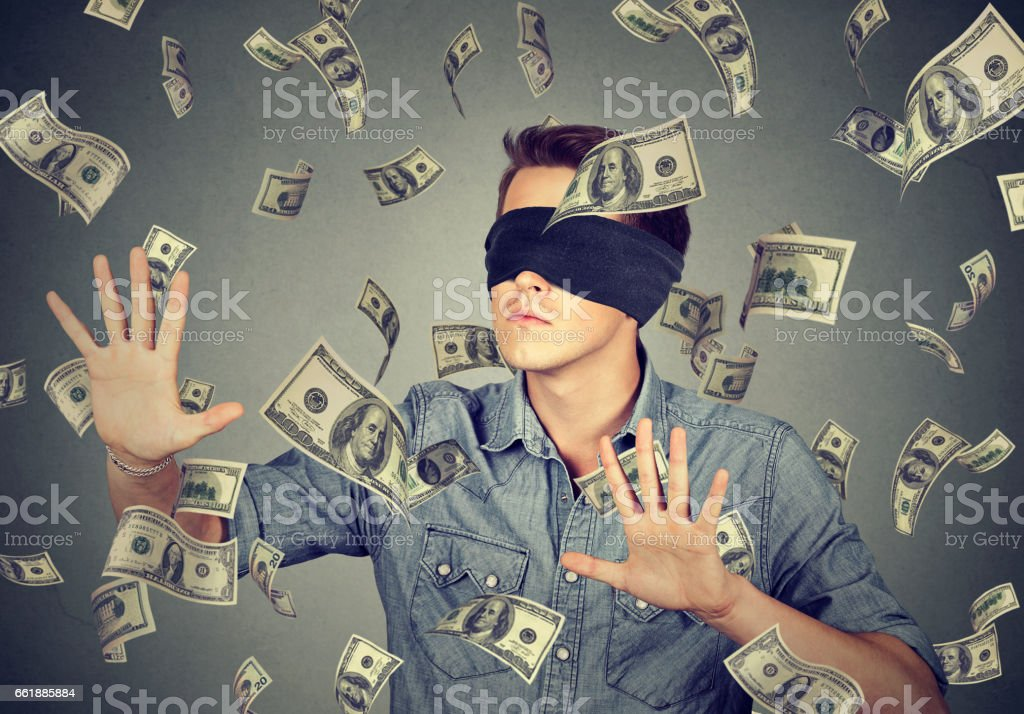 Blindfolded young businessman trying to catch dollar bills banknotes stock photo