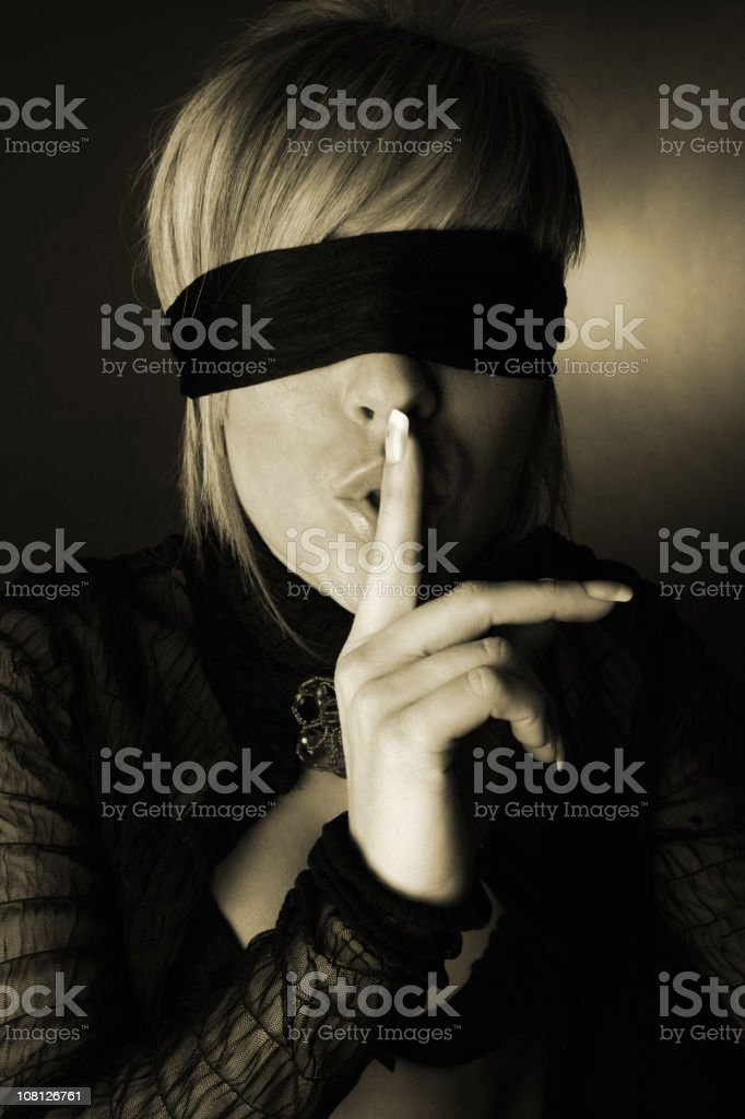 Blindfolded Young Woman Holding Finger to Lips, Sepia Toned royalty-free stock photo