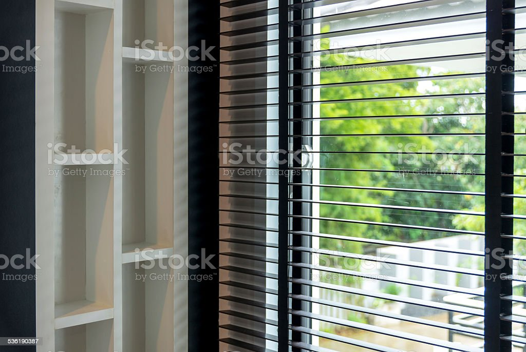 blinds inside a window being opened with bedroom interior stock photo