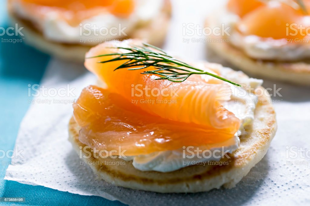 Blinis with white cream cheese and salmon stock photo