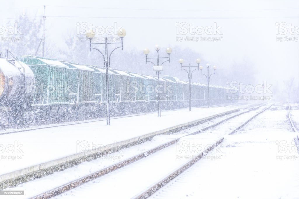 Blizzard on railway, freight train in snow stock photo