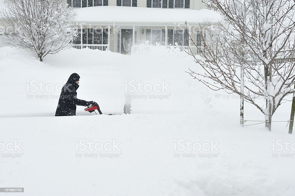 Blizzard Snow, Man using Snowblower stock photo