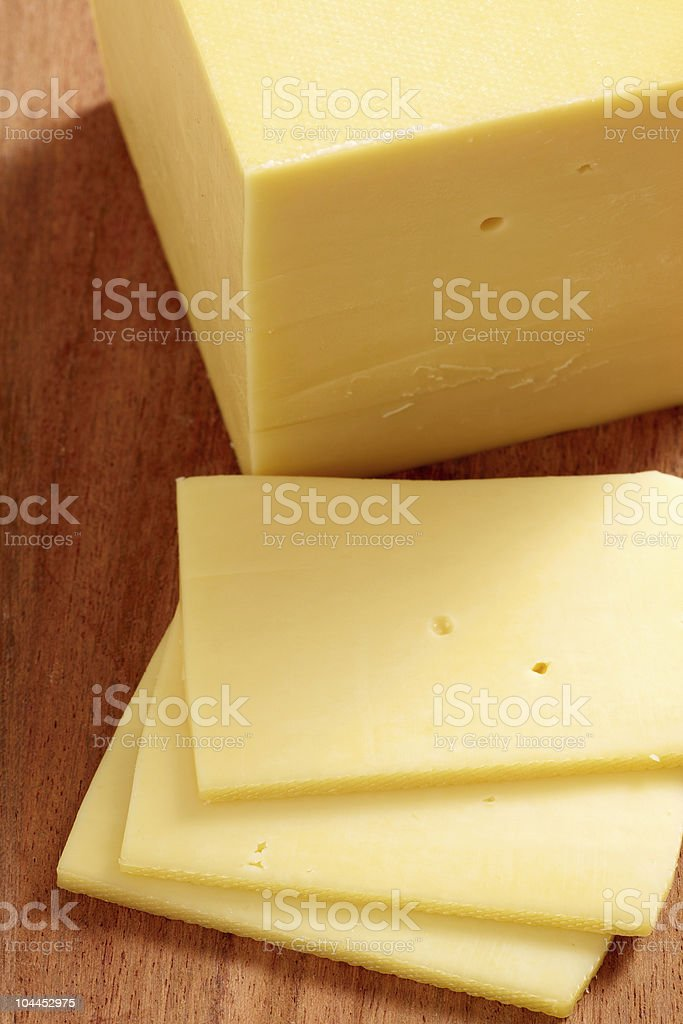 A block of cheddar cheese with three slices cut off royalty-free stock photo