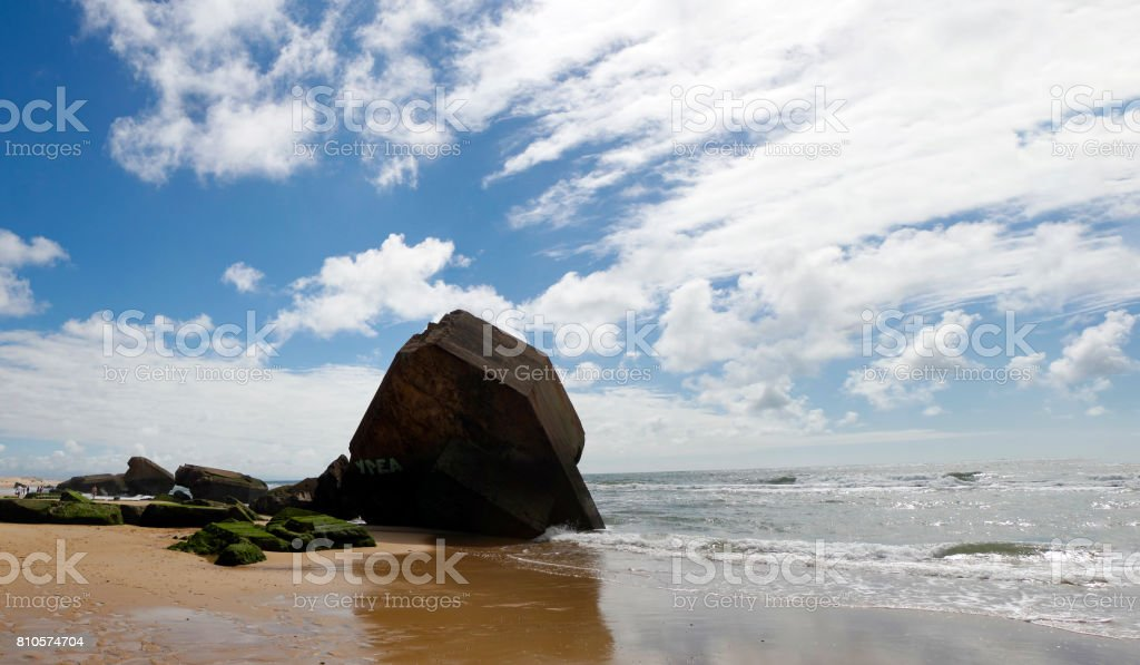 Blockhouse on the beach with blue sky and clouds stock photo