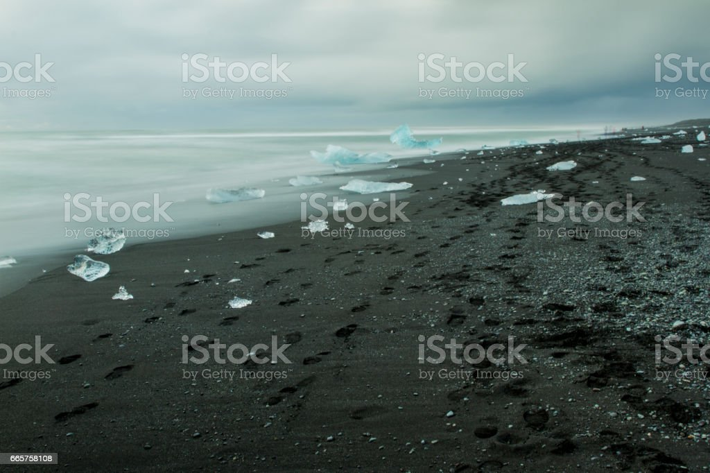 Blocks of ice and footprints on black sand beach stock photo
