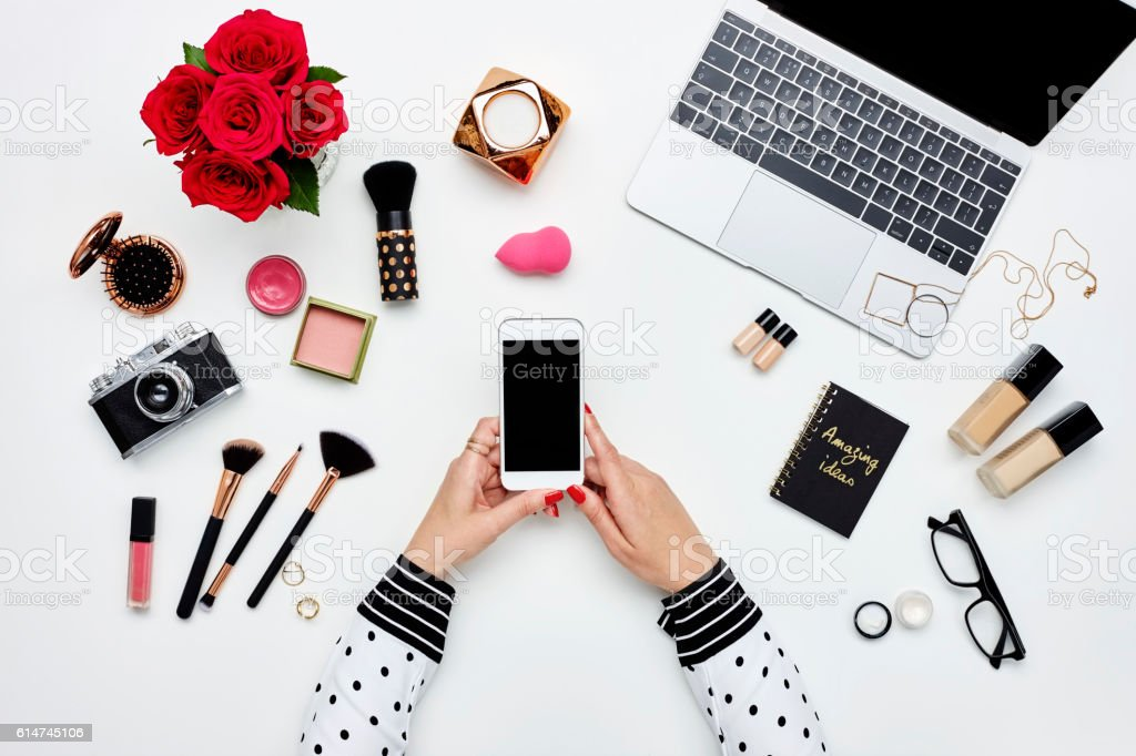 Blogger holding smart phone surrounded with beauty products stock photo
