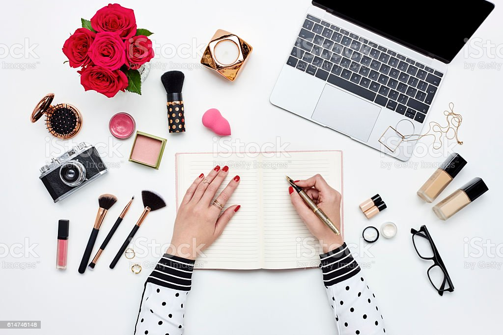 Blogger writing in book surrounded with beauty products stock photo