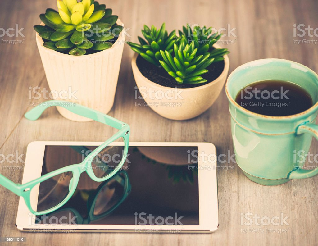 Bloggers business desk with digital tablet, glasses, cacti and coffee stock photo