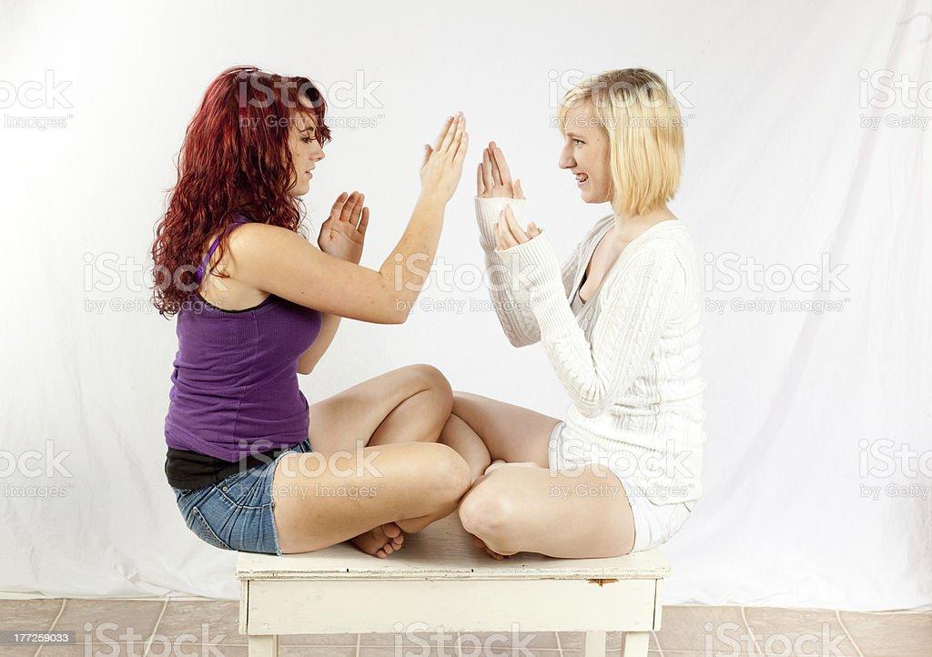 Blond and Redhead girls playing patty-cake stock photo