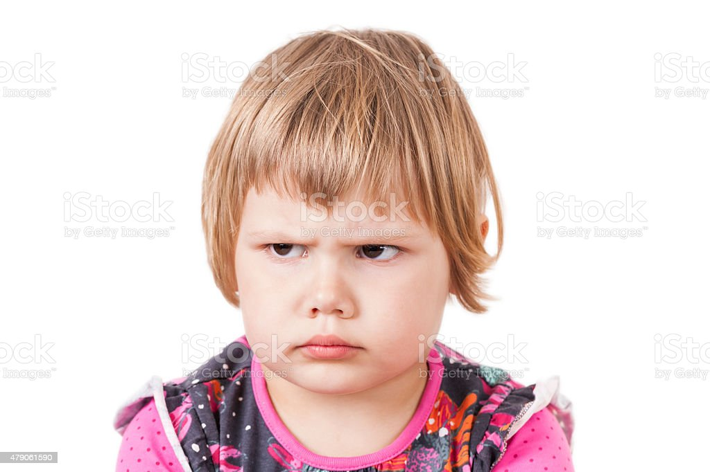 Blond baby girl angry frowns, studio portrait stock photo