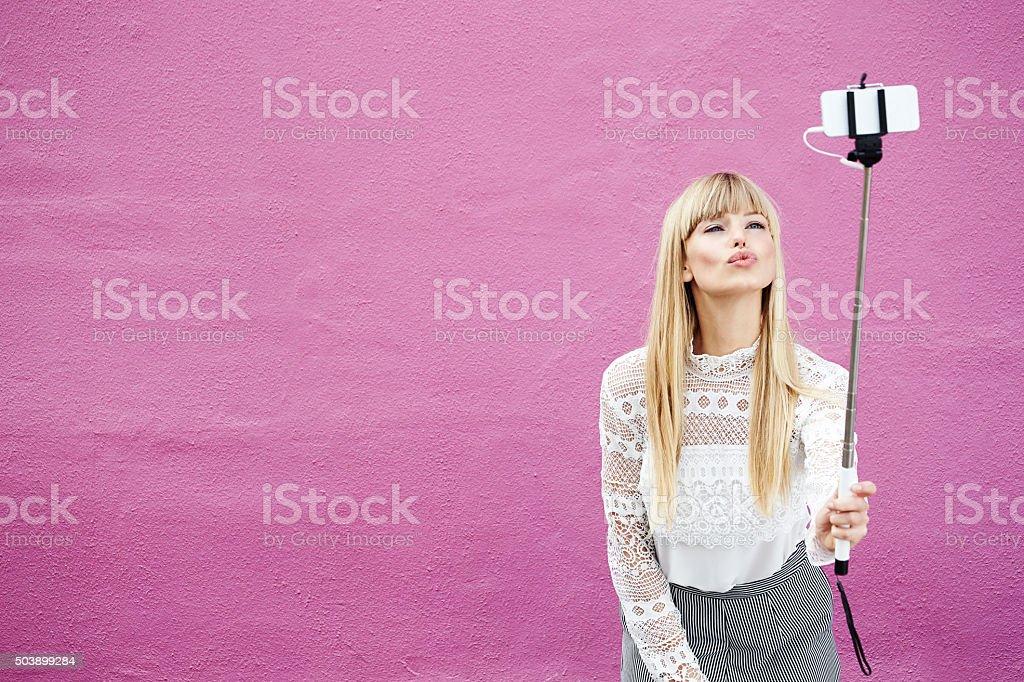 Blond beauty kissing for selfie stock photo