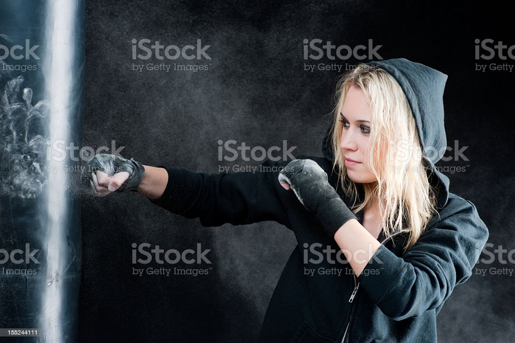 Blond boxing woman in black punching bag royalty-free stock photo
