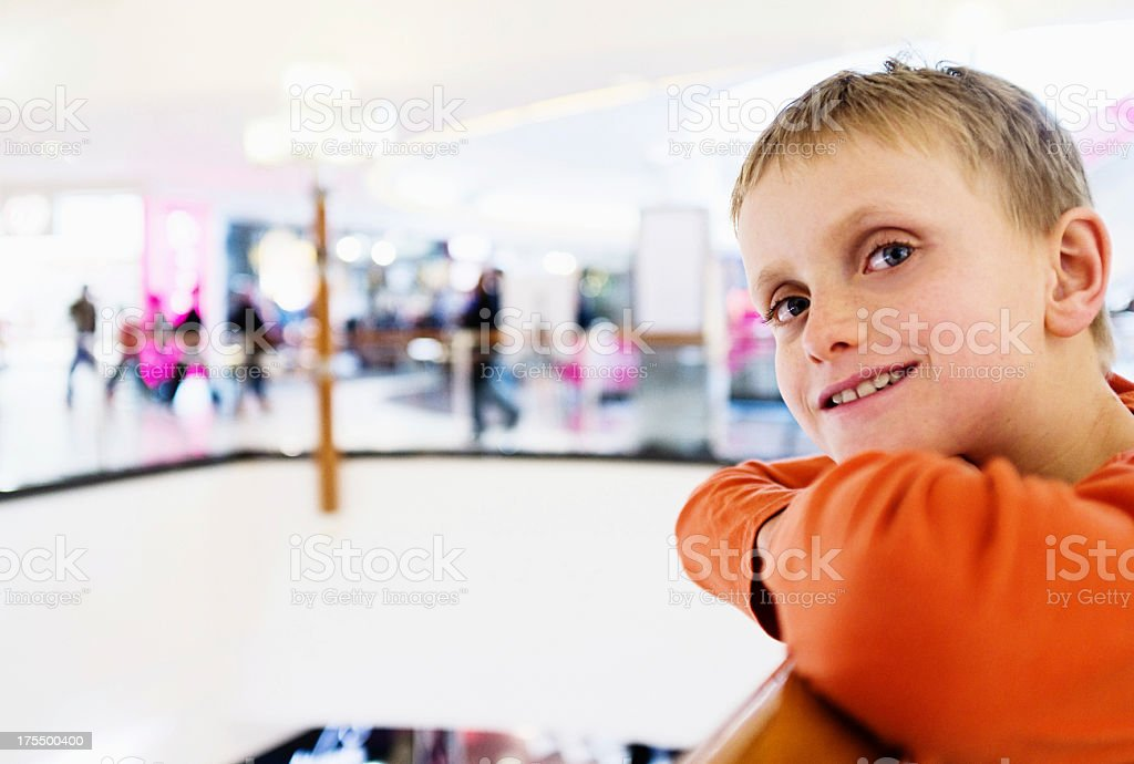 Blond boy at shopping mall leans over central well smiling stock photo
