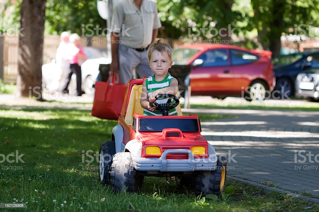 blond boy driving a toy car royalty-free stock photo