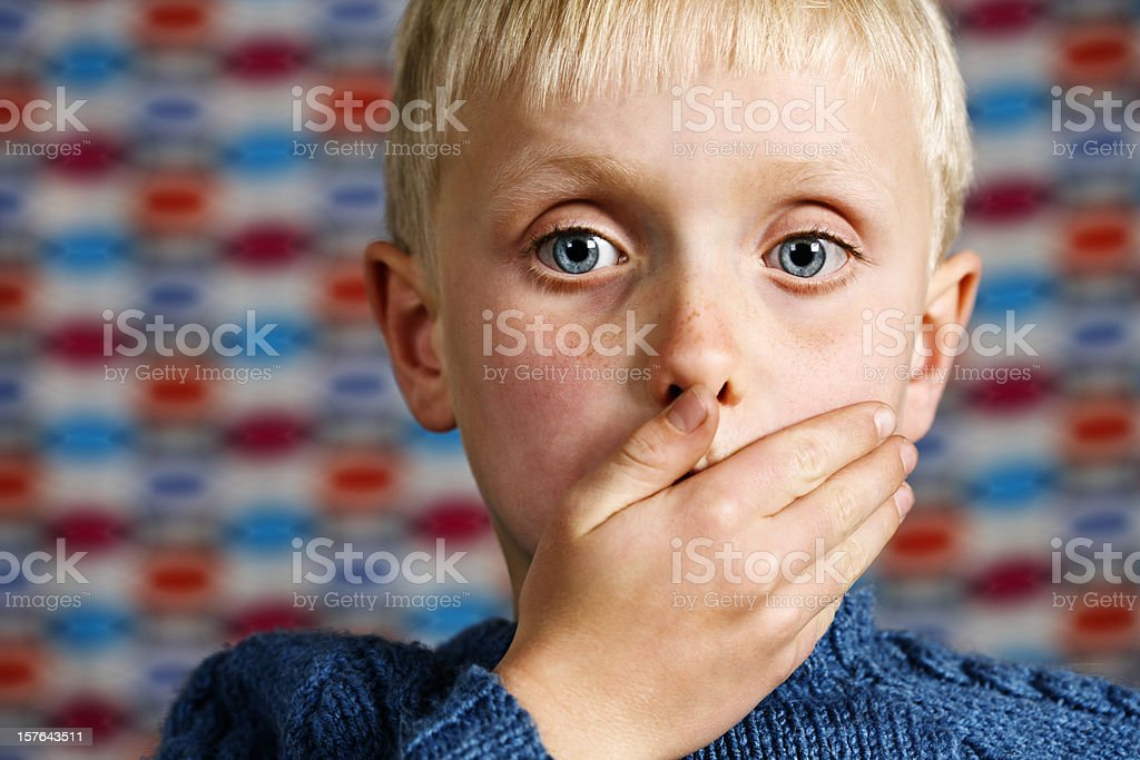 Blond boy makes the 'Speak no Evil' gesture stock photo