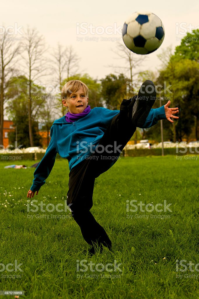 Blond boy play soccer at the park royalty-free stock photo