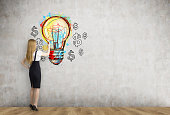 Blond businesswoman and light bulb with dollars