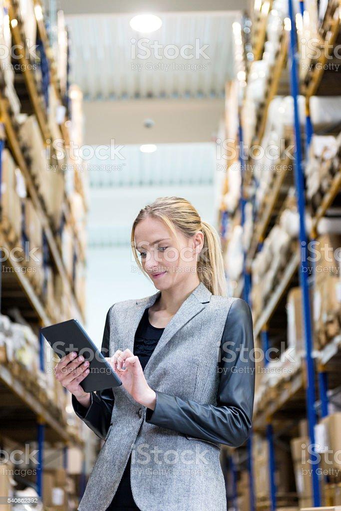 Blond businesswoman working on tablet in storage stock photo