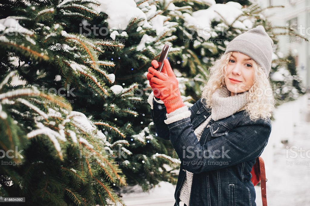 Blond curly girl making photo on smartphone, winter stock photo
