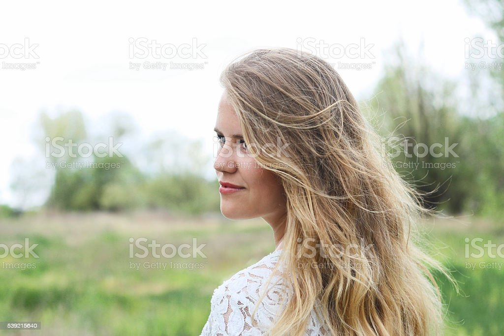 blond cute girl with beautiful wild hair enjoys the freshness stock photo