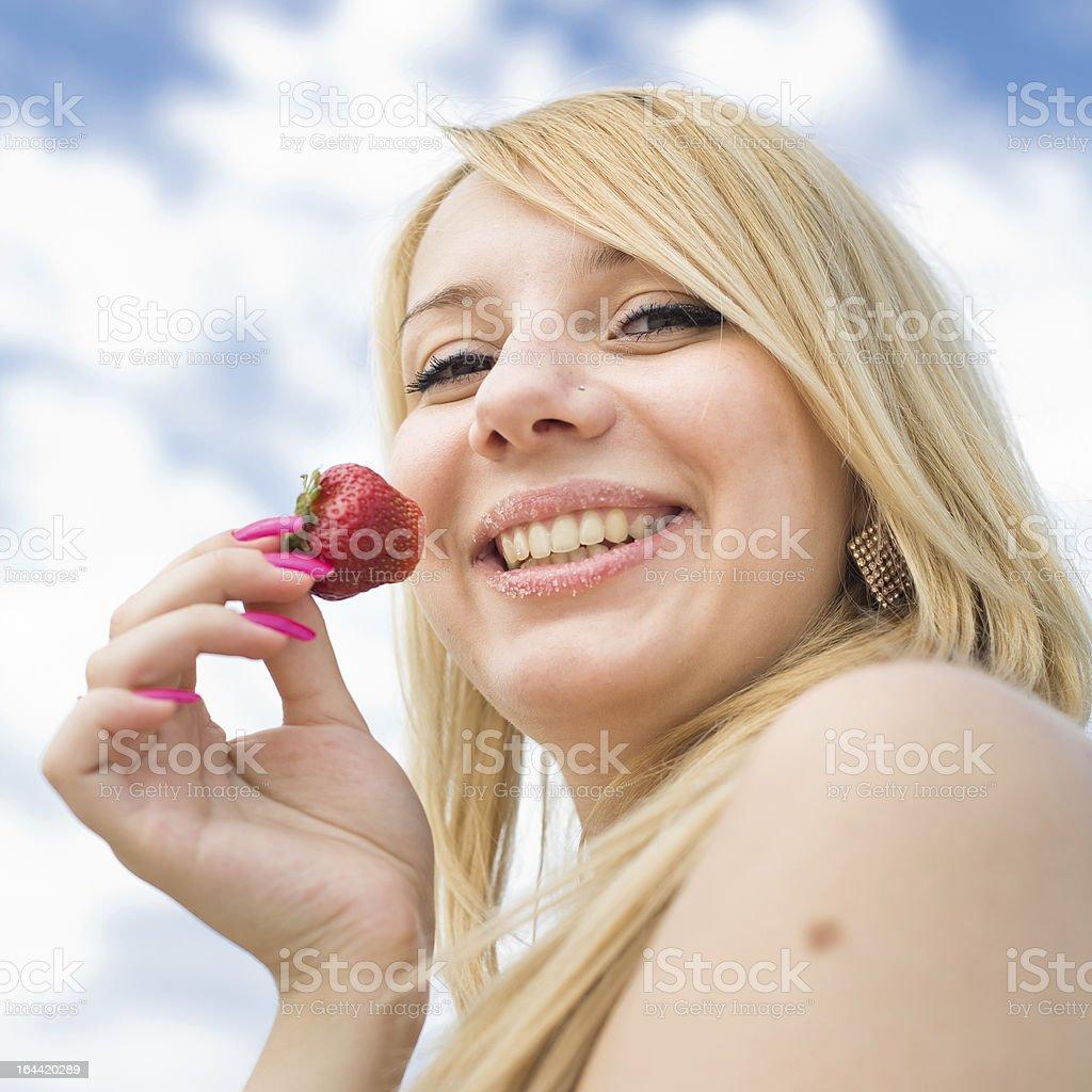 Blond eats strawberry royalty-free stock photo