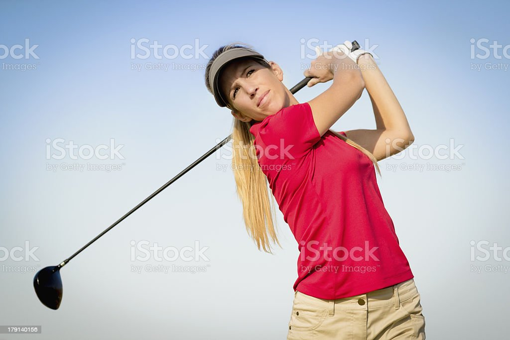 Blond female golfer in the finishing position royalty-free stock photo