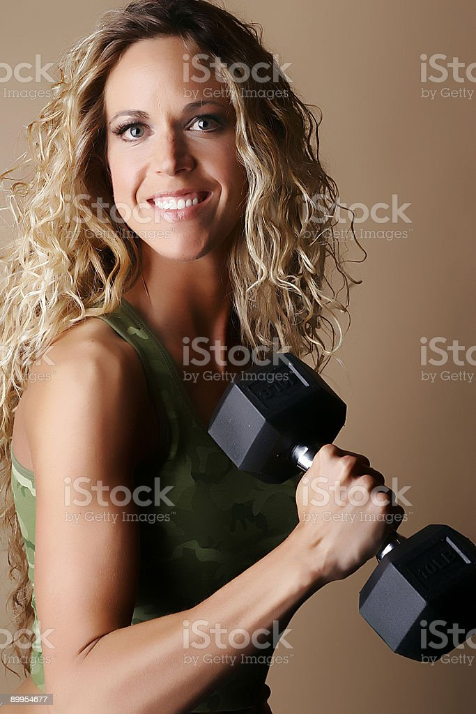 Blond female model lifting a dumbbell royalty-free stock photo