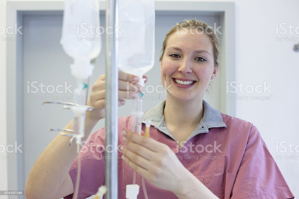 blond female nurse prepares an IV Drip stock photo