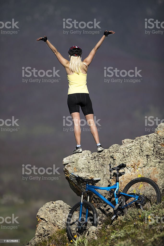 Blond Female On Mountain Rock Celebrating Bicycle Climb To Top stock photo