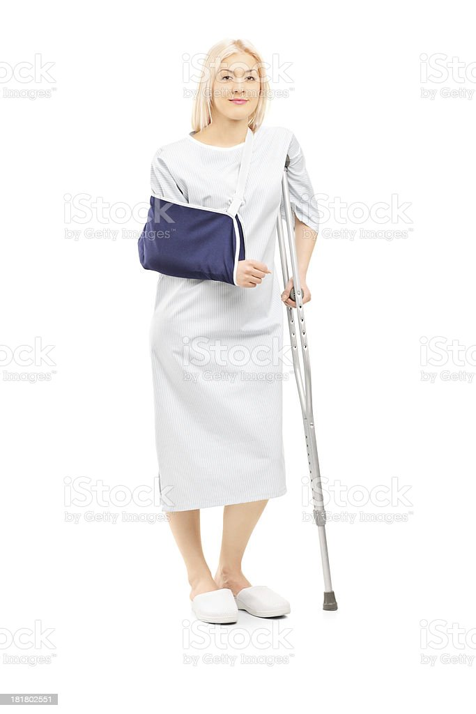 Blond female patient in gown with broken arm and crutch royalty-free stock photo