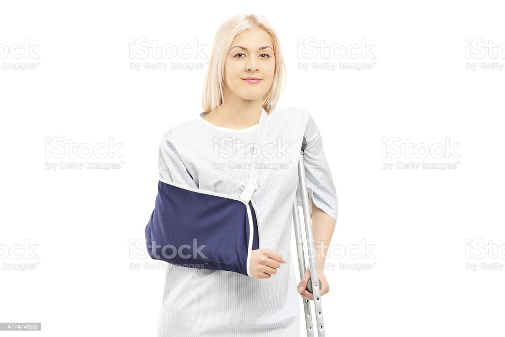 Blond female patient in hospital gown with broken arm royalty-free stock photo