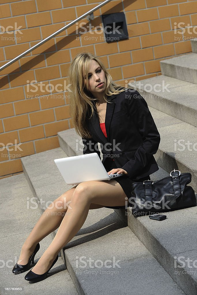 Blond Female Student working with Netbook on Stairs Outdoor royalty-free stock photo