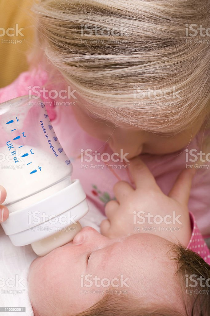 blond girl feeding her newborn brother royalty-free stock photo