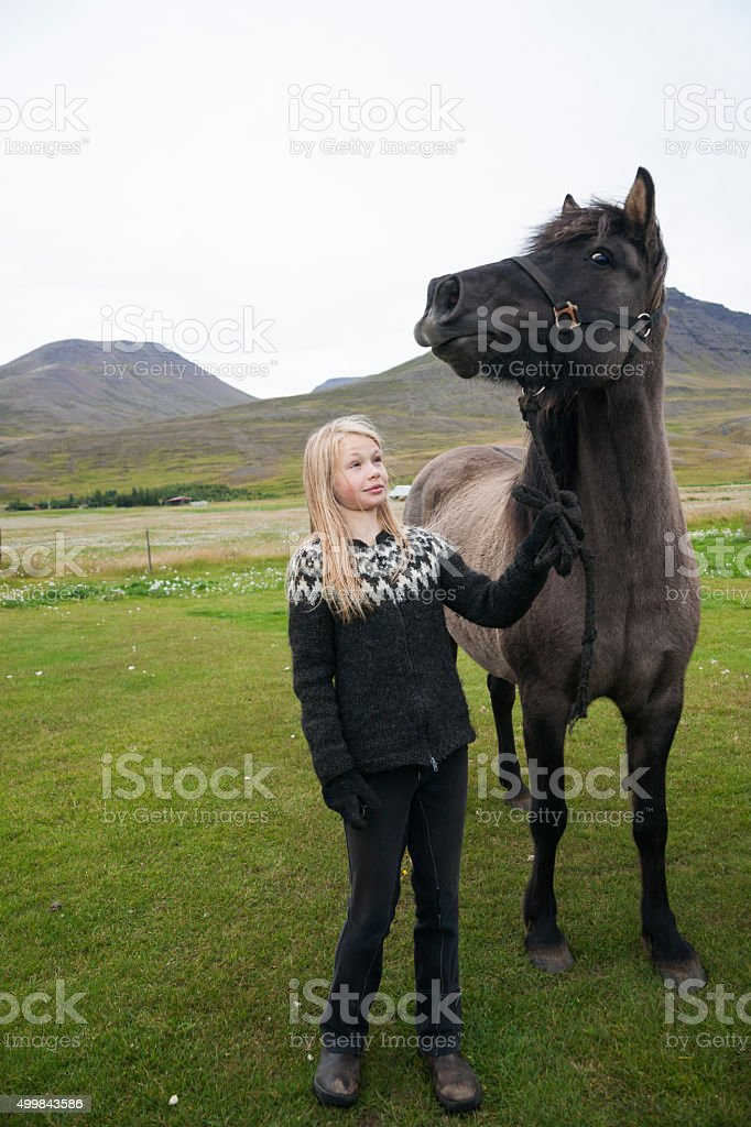 Blond girl hold back an Icelandic horse stock photo