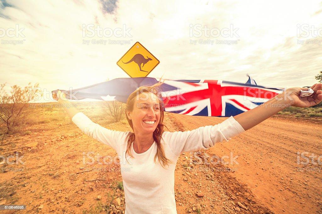 Blond girl holding Australian flag in air near Kangaroo sign stock photo